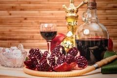 Aún-vida con la cachimba, el vino, el granate y los dulces Foto de archivo libre de regalías
