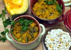 Aún-vida con la calabaza frita hecha en casa con la zanahoria y las habas verdes en potes de arcilla del color Foto de archivo libre de regalías