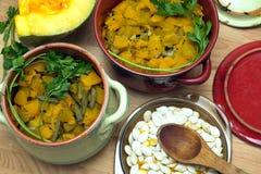 Aún-vida con la calabaza frita hecha en casa con la zanahoria y las habas verdes en potes de arcilla del color Imagenes de archivo