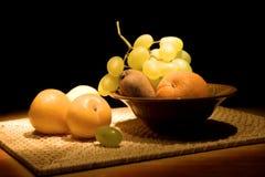 Aún-vida con la fruta en un florero fotografía de archivo