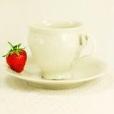 Aún-vida con la taza, el platillo y la fresa Imágenes de archivo libres de regalías