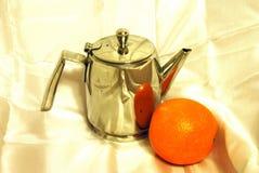 Aún-vida con la tetera y la naranja. Fotos de archivo libres de regalías