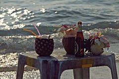 Aún-vida con las bebidas en la playa Foto de archivo