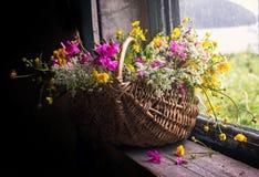 Aún-vida con las flores salvajes de un manojo en una cesta Fotos de archivo