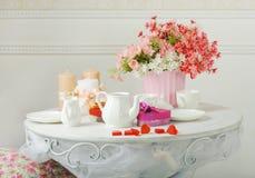 Aún-vida con las flores, las tazas y la caldera en la tabla blanca Imagen de archivo libre de regalías