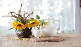 Aún-vida con leche en un jarro transparente y un ramo de sunfl Foto de archivo libre de regalías