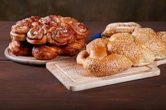 Aún-vida con los rollos y las empanadas en una tabla de cocina Imagen de archivo libre de regalías