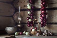 Aún-vida con los utensilios y las cebollas rurales en casa vieja Imágenes de archivo libres de regalías