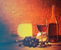 Aún-vida con queso, las uvas y el vidrio de vino rojo Foto de archivo