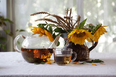 Aún-vida con té en una tetera transparente y un ramo de sol Fotos de archivo
