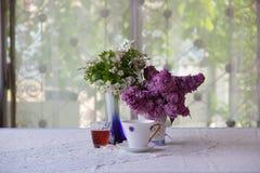 Aún-vida con té, vino y un ramo de la lila Fotografía de archivo libre de regalías