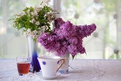 Aún-vida con té, vino y un ramo de la lila Imagen de archivo