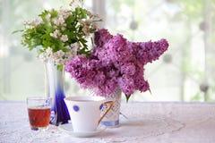 Aún-vida con té, vino y un ramo de la lila Fotos de archivo