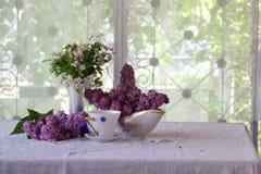 Aún-vida con té y un ramo de la lila Imágenes de archivo libres de regalías