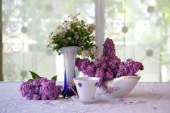 Aún-vida con té y un ramo de la lila Fotografía de archivo