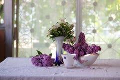 Aún-vida con té y un ramo de la lila Fotos de archivo