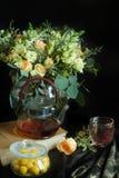 Aún-vida con un ramo de flores y de una caldera y los caramelos en un tarro Imagen de archivo