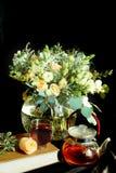 Aún-vida con un ramo de flores y de una tetera con té en un fondo oscuro Imagen de archivo libre de regalías