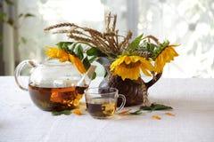 Aún-vida con un ramo de girasoles y de té Fotografía de archivo libre de regalías