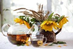 Aún-vida con un ramo de girasoles y de té Foto de archivo