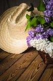 Aún-vida con un ramo de lilas y de un sombrero de paja Fotografía de archivo libre de regalías