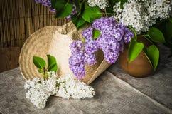 Aún-vida con un ramo de lilas y de un sombrero de paja Foto de archivo libre de regalías