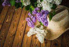 Aún-vida con un ramo de lilas y de un sombrero de paja Imágenes de archivo libres de regalías