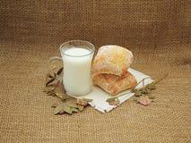 Aún-vida con un vidrio de la leche, del pan hecho en casa y del trébol secado Fotografía de archivo