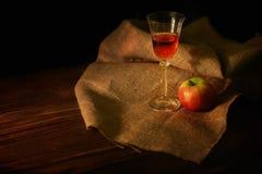 Aún-vida con un vidrio del vino y de una manzana en oscuro Foto de archivo libre de regalías