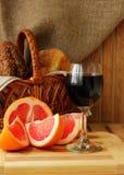 Aún-vida con un vidrio del vino y del pomelo Foto de archivo libre de regalías