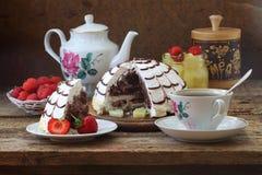 Aún-vida con una empanada de Pancho, del té y de una fresa fresca Fotos de archivo