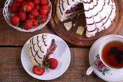 Aún-vida con una empanada, té y una fresa fresca Fotos de archivo