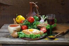 Aún-vida con una empanada, verduras frescas y un vino rojo Imágenes de archivo libres de regalías