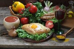 Aún-vida con una empanada, verduras frescas y un vino rojo Foto de archivo libre de regalías