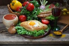 Aún-vida con una empanada, verduras frescas y un vino rojo Foto de archivo