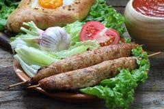 Aún-vida con una empanada y un ljulja-kebab Foto de archivo libre de regalías