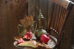 Aún-vida con una granada, una empanada y un jarro de cobre Fotografía de archivo libre de regalías