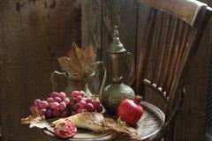 Aún-vida con una granada, uvas y un jarro de cobre Fotografía de archivo libre de regalías