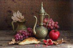 Aún-vida con una granada, uvas y un jarro de cobre Foto de archivo libre de regalías