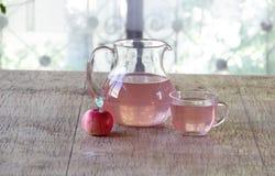Aún-vida con una manzana y una compota en un jarro transparente Foto de archivo libre de regalías