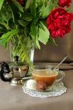 Aún-vida con una taza de café, de dulces y de peonías Foto de archivo