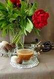 Aún-vida con una taza de café, de dulces y de peonías Fotografía de archivo libre de regalías