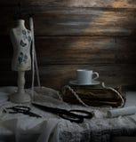 Aún-vida con una taza de café, de tijeras, de costura del maniquí y de cordón en un fondo de paredes de madera ásperas vendimia Imagen de archivo