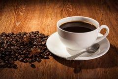 Aún-vida con una taza de café sólo y de granos de café asados Imagen de archivo libre de regalías