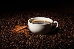 Aún-vida con una taza de café sólo y de granos de café asados Imagenes de archivo