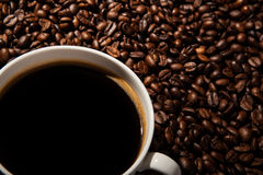 Aún-vida con una taza de café sólo y de granos de café asados Foto de archivo libre de regalías