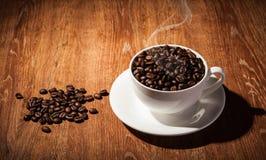 Aún-vida con una taza de granos de café Imagenes de archivo