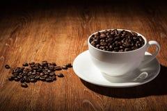 Aún-vida con una taza de granos de café Foto de archivo