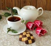Aún-vida con una taza de té negro, de galletas y de tulipanes Fotos de archivo libres de regalías