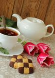 Aún-vida con una taza de té negro, de galletas y de tulipanes Imágenes de archivo libres de regalías